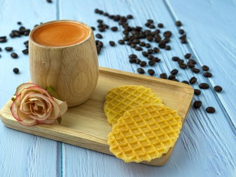 Warm offee in a brown bamboo cup with waffles and brown sugar.