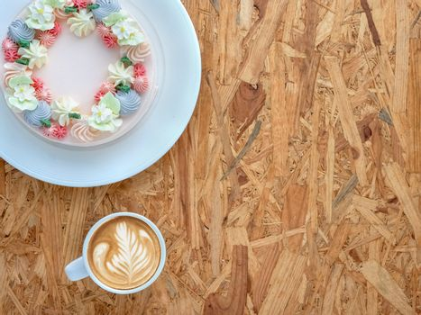 Beautifully decorated cake with cup of coffee on rustic wooden board background. top view, flat lay, copy space.