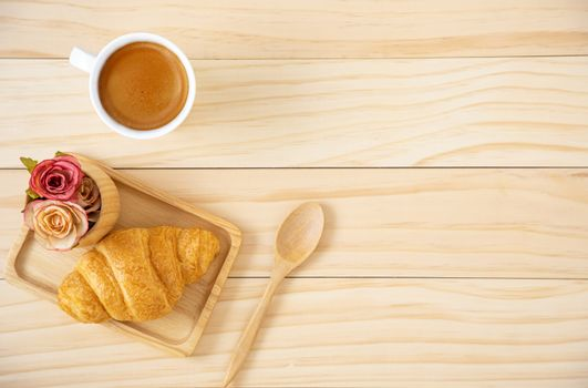 A piece of butter croissant on a squate wooden plate and a cup of coffee in white ceramic mug. Wooden background.