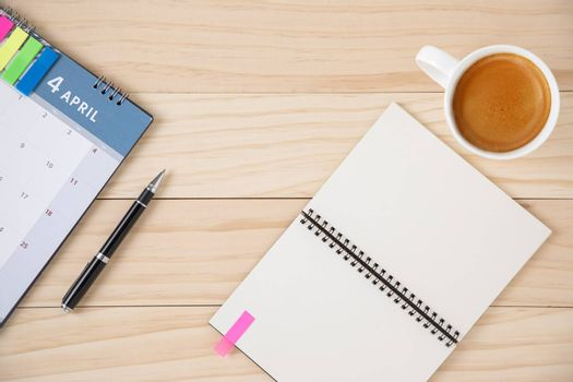A blank notebook, a calendar, and a cup of coffee in white ceramic cup. Wooden background.
