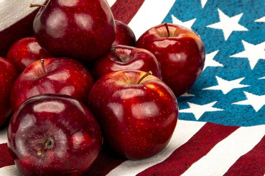 Pile of red apples on a cotton cloth with white stars on blue background and red and white stripes pattern.
