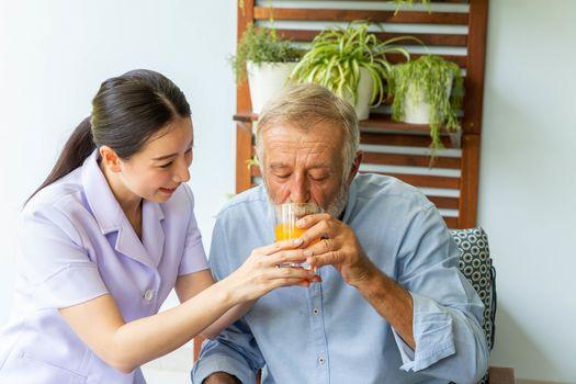 Nurse assist senior man having a cup of orange juice