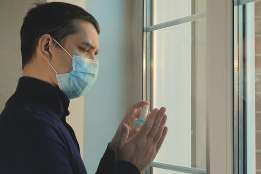 Coronovirus protection during a pandemic. COVID-19 concept. Man returns from the street to the house in a medical mask and disinfects his hands after a walk during coronavirus pandemic, close up.