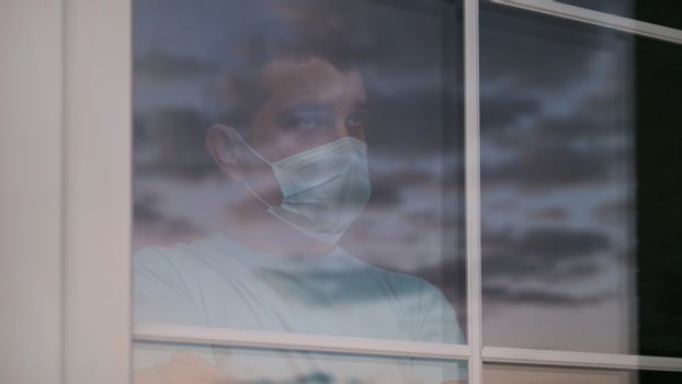 Home quarantine, self-isolation because of the Coronavirus disease, COVID-19. Man in a medical mask near the window. Boredom, sad, depression and suicidal mood, during quarantine. View through glass.