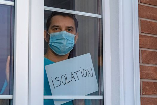 Man in a medical mask looks at the camera through a window. Self-isolation in the house. Young attractive man in a blue clothes with medical mask showing a nameplate with the lettering - ISOLATION.