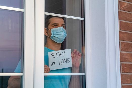 Young man in a medical mask stands at home outside the window and shows a nameplate with the lettering Stay at home. Calls for self-isolation due to pandemic and risk of coronavirus infection COVID-19