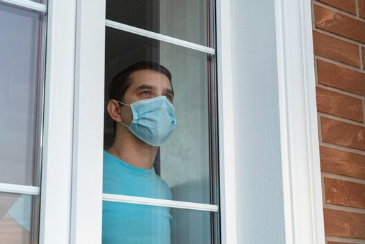 Coronavirus. Sick man of coronavirus looking through the window and wearing mask protection and recovery from the illness in home. Quarantine isolation. Sick isolated at home to prevent infection.