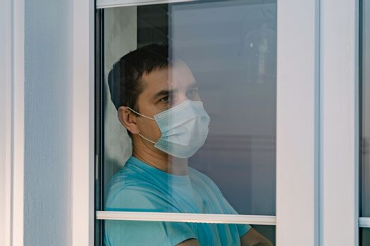 Sad man wearing face mask and looking out of window at home quarantine caused by coronavirus. Man in a medical mask looks out the window thoughtfully. Boredom and depression during quarantine COVID-19