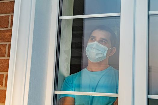 Infected man in medical mask on self-isolation looks at the street through the window of a house. Man in medical mask stay at home. Self-isolation in the house. Quarantined, isolated from society.