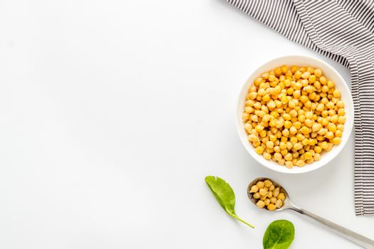Raw chickpeas in bowl on white kitchen table from above copy space