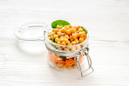 Vegan lunch. Chickpeas, carrot, tomato in glass jar on white table