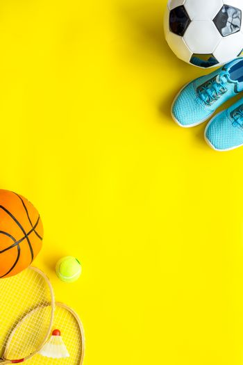 Sport games equipment - balls, sneakers, rockets - on yellow top view copy space
