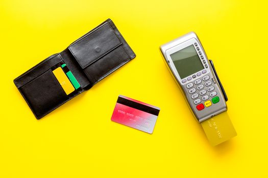 Payment by credit card. Terminal on yellow background top-down