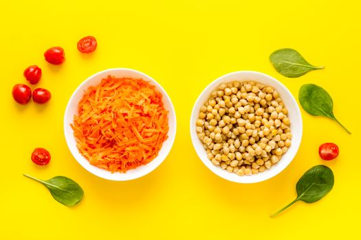 Vegetarian meal. Chickpeas and carrot in bowls on yellow table top view