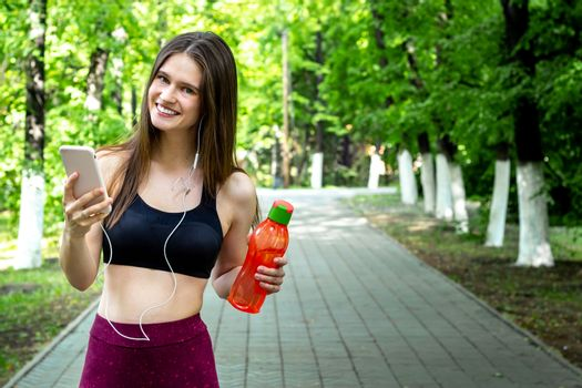 Sport young woman - smiling, with headpnones and water - outdoor in park