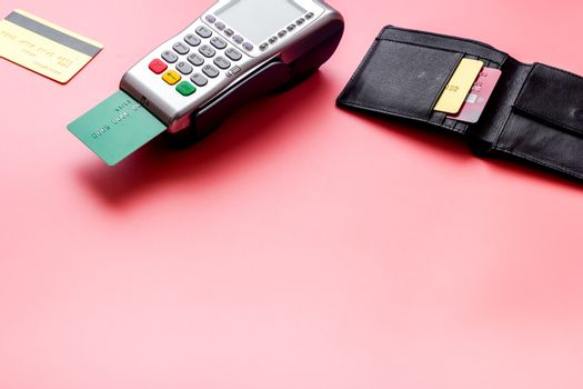 Payment by credit card. Terminal on pink table copy space