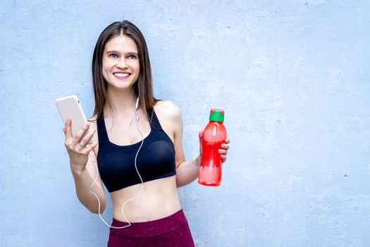 Fitness girl listening to music - smiling, with water - blue wall, copy space