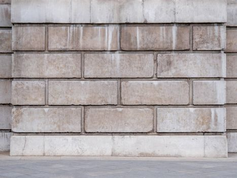 Dirty white cement blocks with concrete slabs and a curb on floor. Abstract empty urban interior background with gray brick wall and concrete floor tiling. White brick wall background with copy space.