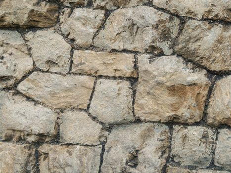 Stone ancient wall paved with cobble stones, closeup. Old brown and gray cobblestone wall texture. Natural Stone Wall Texture. Stone wall background. Background of stone wall of boulders and pebbles.