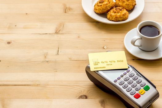 Payment transactions. Terminal and credit card on cafe wooden table copy space