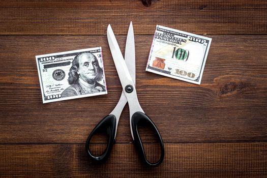 Decline of dollar exchange rate. Scissors cut dollars banknote