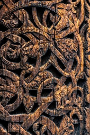 Ornaments of ancient vikings on a wooden surface. External wooden wall carved decoration of medieval Stave church with viking motifs covered with tar. Detailed pattern of ancient vikings in Norway.