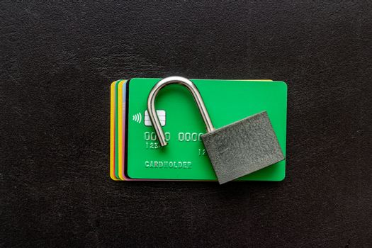 credit card hacked - security lock open - on black table top view