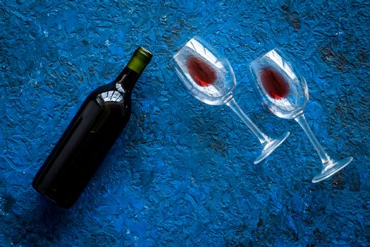Wine bottle and glasses on blue background from above copy space