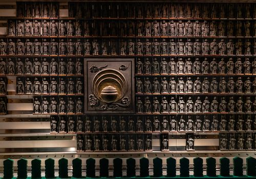 a wall full of rows of statues of Buddha in a warrior position