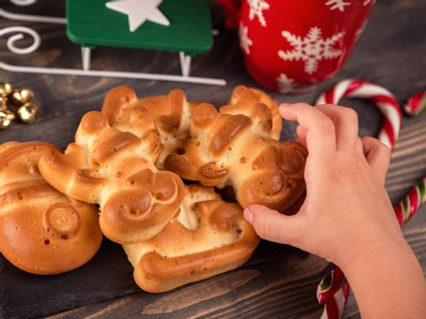 Children hand takes ruddy gingerbread in the shape of a deer. Homemade cookies baked to Christmas. Table top shot of a nicely decorated Christmas cookies on a rustic wooden table. Top view, closeup.
