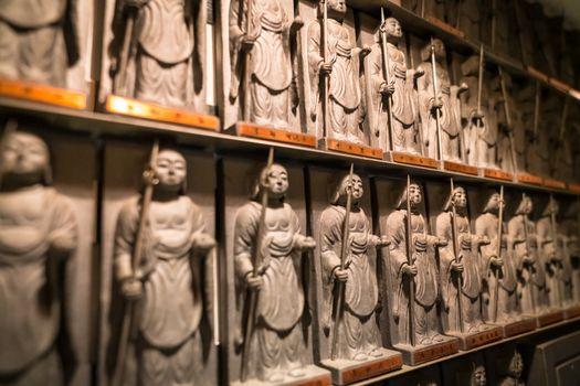 Closeup of a shelf full of warrior Buddha statues