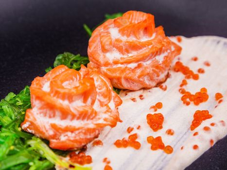 Baked salmon in cream sauce garnished with hiyashi algae and red caviar, served on a black plate in a restaurant. Salmon fillet with green salad and red caviar. Dish salmon on dark background, closeup