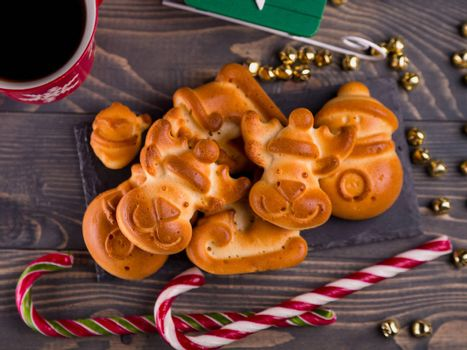 Greeting card with gingerbread cookies. Close up, top view. Merry Christmas and Happy New Year. Christmas cookies homemade on the brown wooden background. Christmas background with ruddy gingerbread.