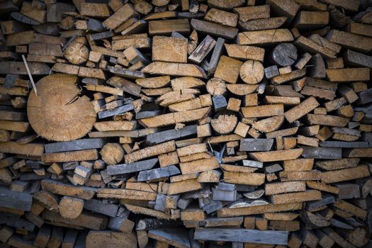 Firewood background - stacked chopped wooden logs backdrop. Background of firewood stack. Pile of chopped fire wood, background. Composition of the cut firewood. Vignette around the perimeter.