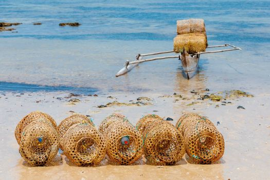 traditional malagasy bamboo woven crustacean fishing trap on beach in Nosy Be. Madagascar countryside scene.