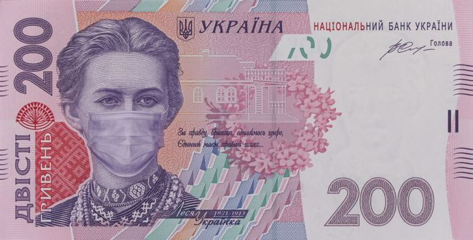 COVID-19 coronavirus in Ukraine. 200 hryvnia banknote with Lesya Ukrainka in a medical mask. Global financial and economic crisis has affected Ukraine. Ukrainian money, coronavirus concept, montage
