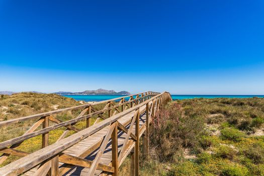 Wooden boardwalk to the beach at bay of Alcudia on Majorca, Spain