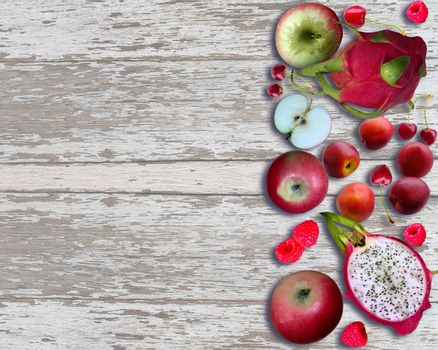 Fresh fruits on light wooden background. Dragon fruit, apple, peach, raspberry and cherry. Top view with copy space
