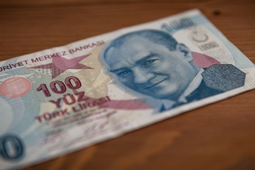 Isolated 100 Turkish Lira Banknote on Wooden Background