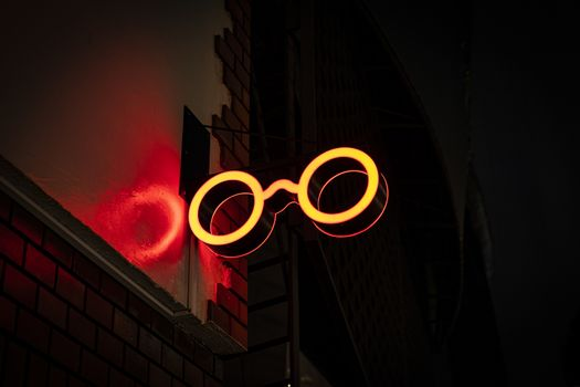 Neon Sign glowing red glasses shape on the street.