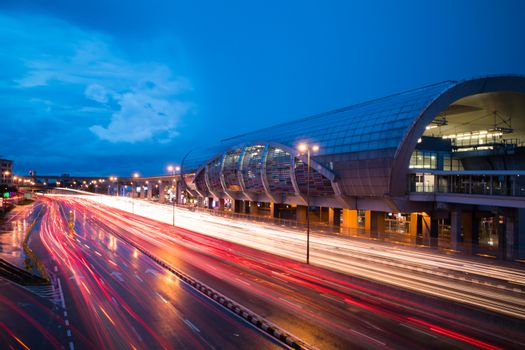 Traffic with light trail next to the train station during blue hour. The road is congested.
