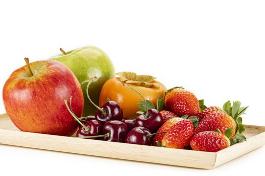 Fresh ripe red, and green apples, persimmon, cherries and strawberries on a wooden plate, isolated on a white background.