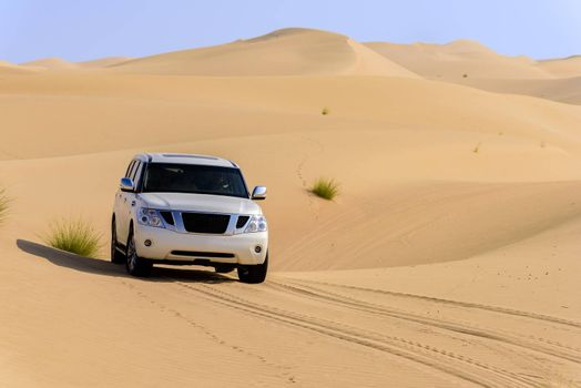A 4x4 off-roading in the red sand dunes of Dubai Emirates, United Arab Emirates