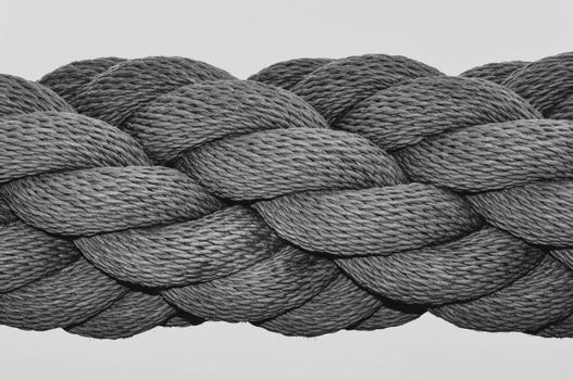 A black and white close up image of a thick industrial rope, with many rope lengths coiled together in a spiral.