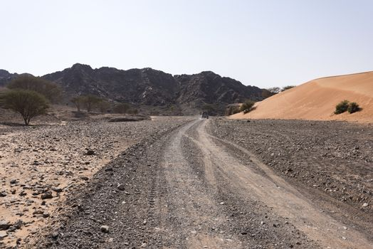 A 4x4 vehicle on a track in Wadi Al Ghail with the mountains and a dunes in the right side, Ras al Khaimah Emirates, United Arab emirates