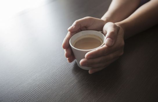 Hands hold a hot cup of coffee on a table