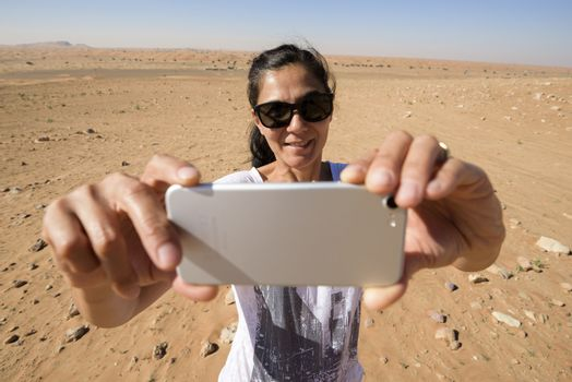 Woman , in the 40s, taking a selfie in the desert with her mobile. We can see the desert with some dunes and stones behind her