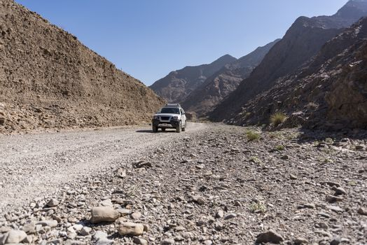 4x4 vehicle in a Wadi (dry riverbed) of Fujairah Emirates, United Arab Emirates. The small SUV is on a path in a small canyon.