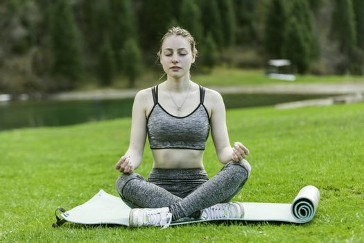 The girl meditates, sits on a rug on a green lawn