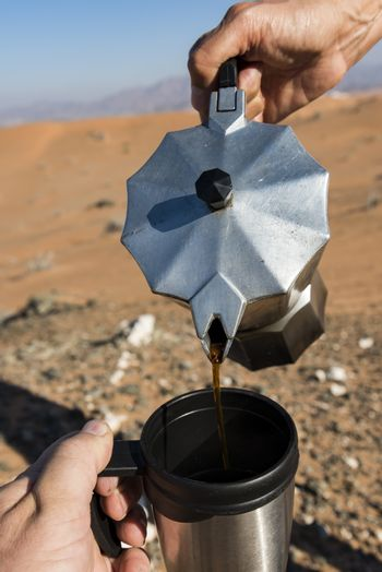 Pouring coffee on a camping cup in the desert (close-up)